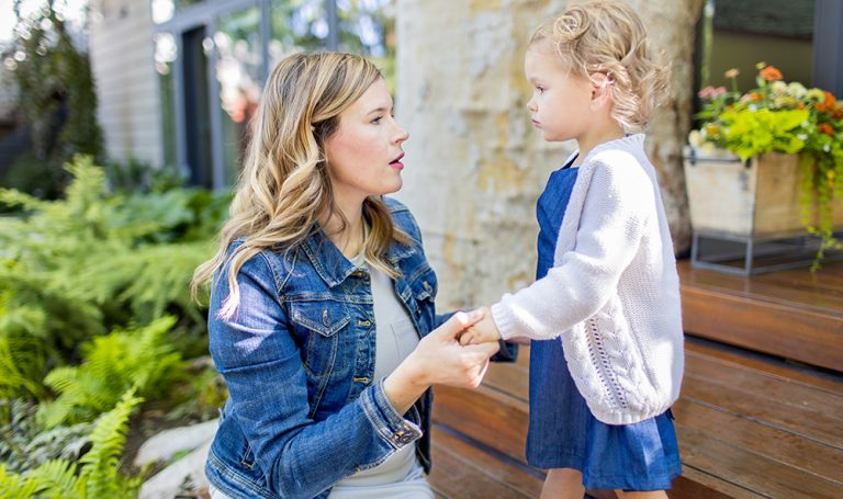 Woman looking at a toddler holding her hands