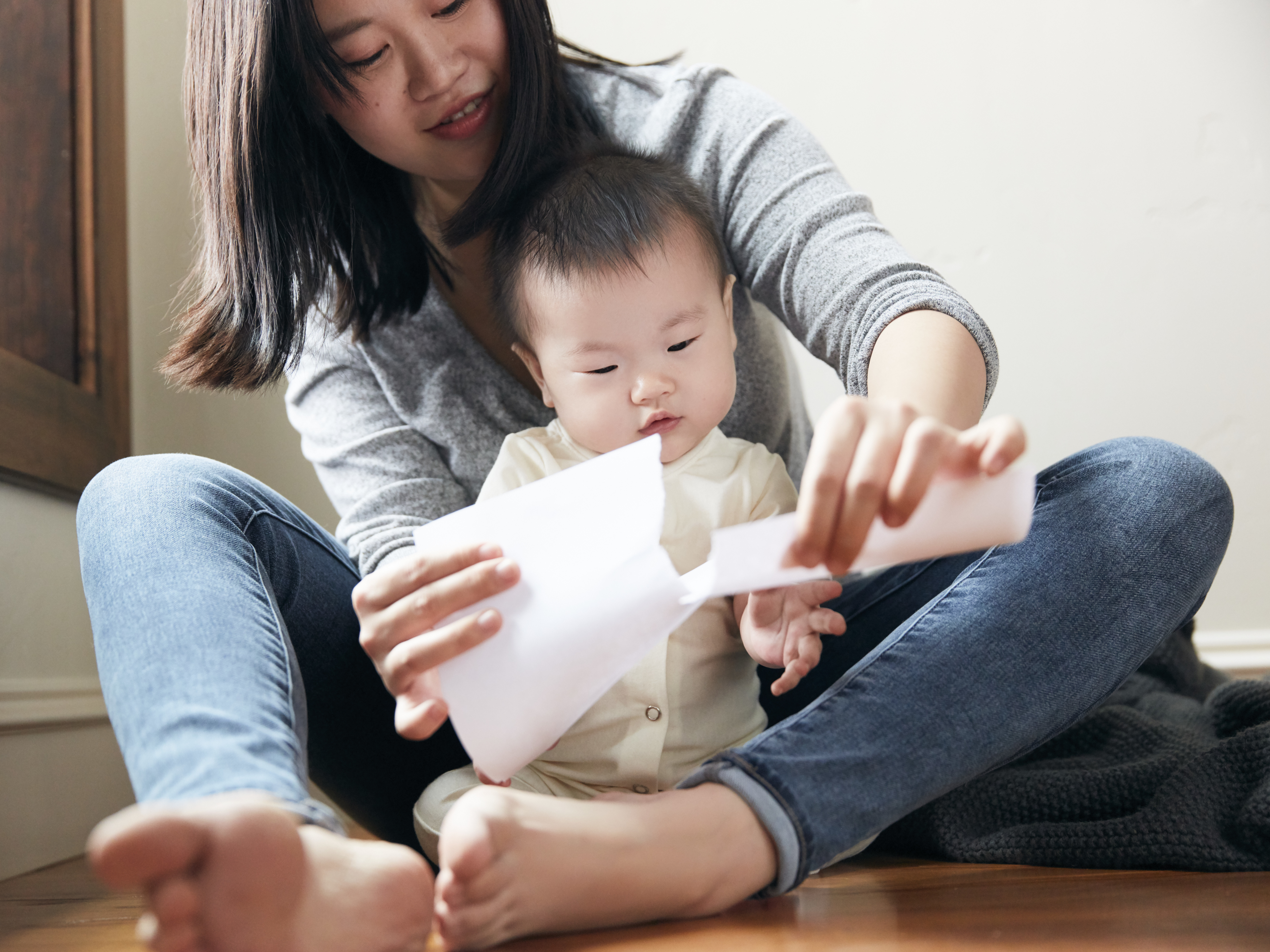 Woman ripping a piece of paper in front of a baby sitting in front of her