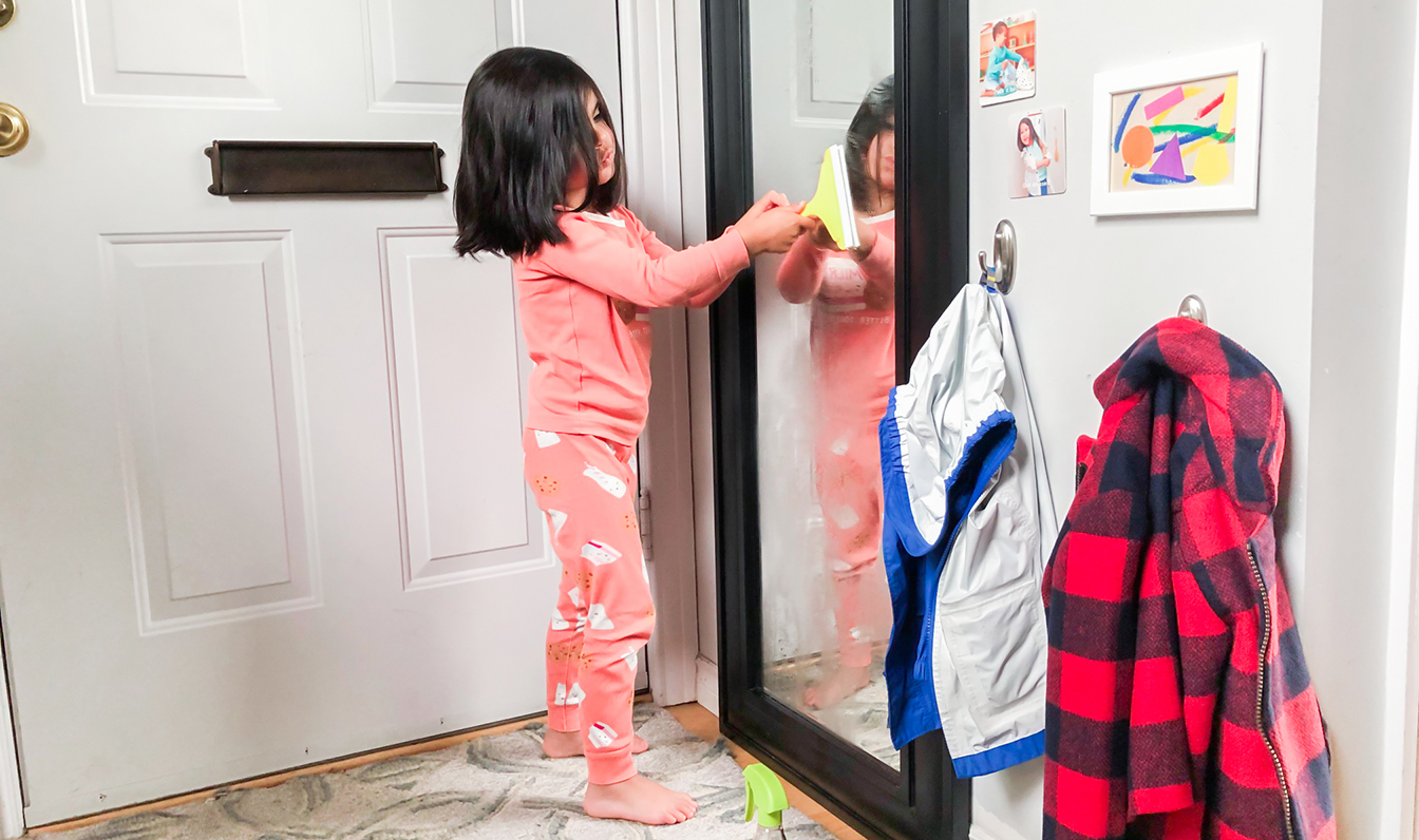 Young child cleaning a window with the Squeaky Clean Squeegee Set by Lovevery