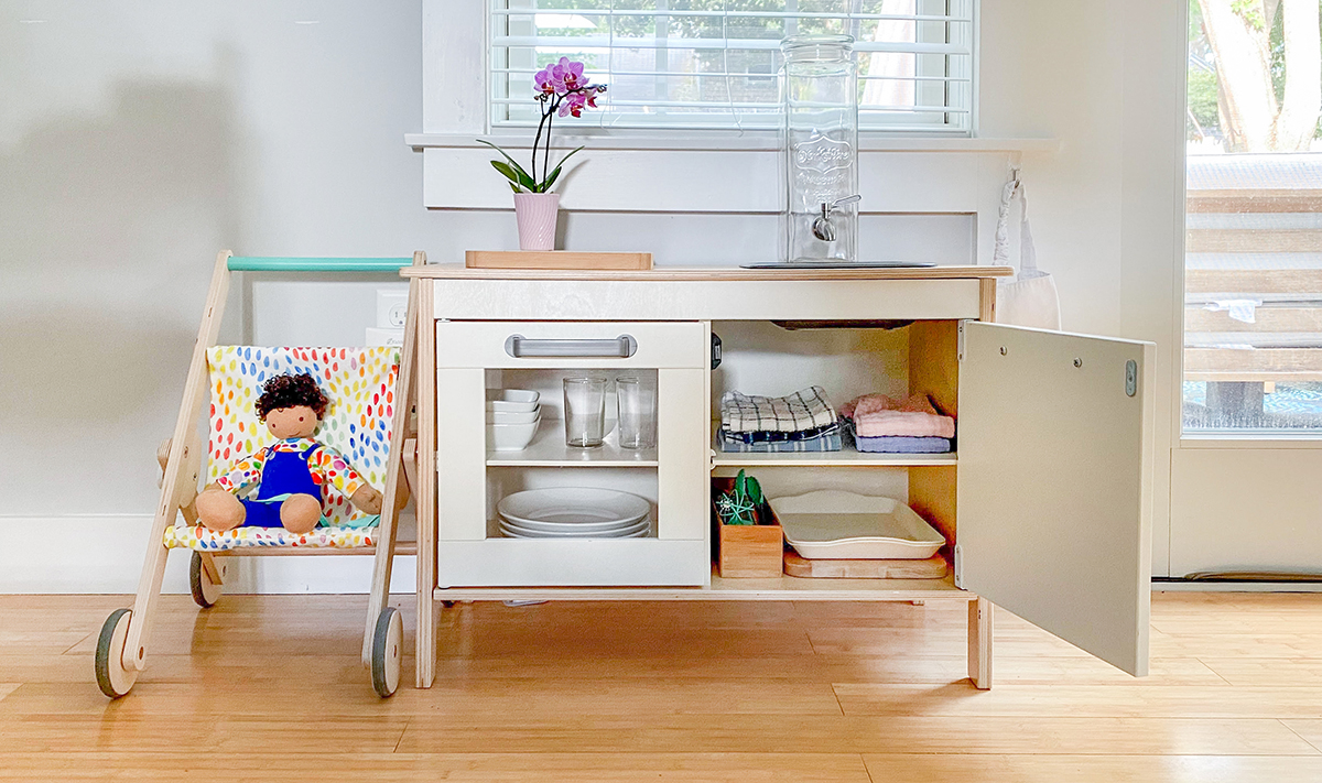 Small storage cabinet holding plates, cups, and napkins next to the Buddy Stroller
