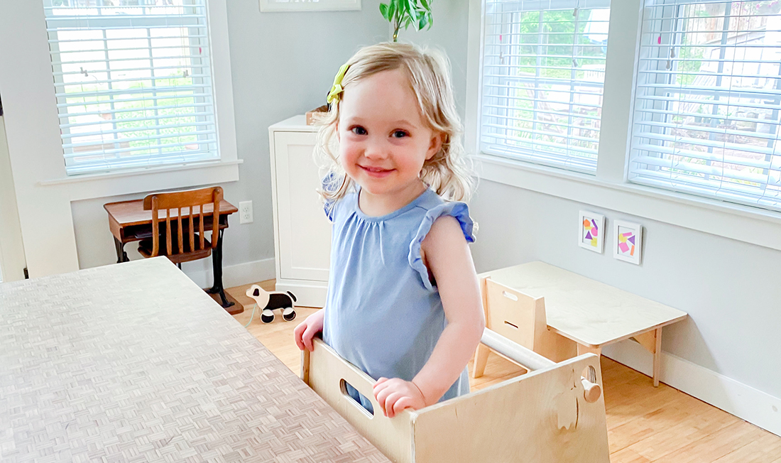 Toddler standing on a stool to get to the kitchen counter