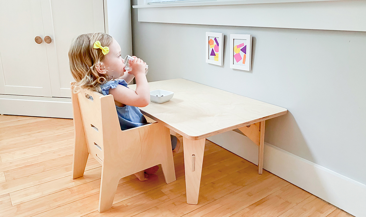 Young child sitting at a wooden table sipping a cup of water