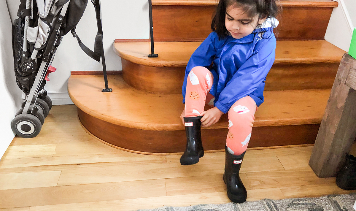Young child putting on rain boots while sitting on the stairs