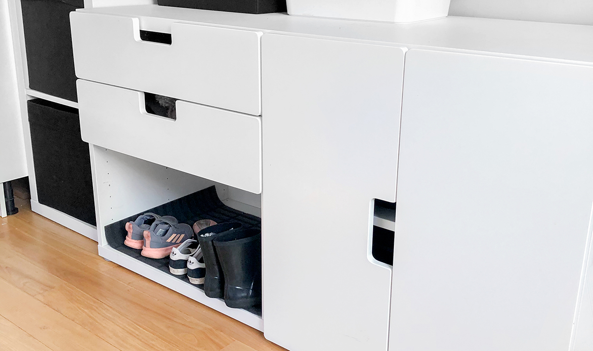 Cabinets and drawers in an entry way with an open spot for shoes