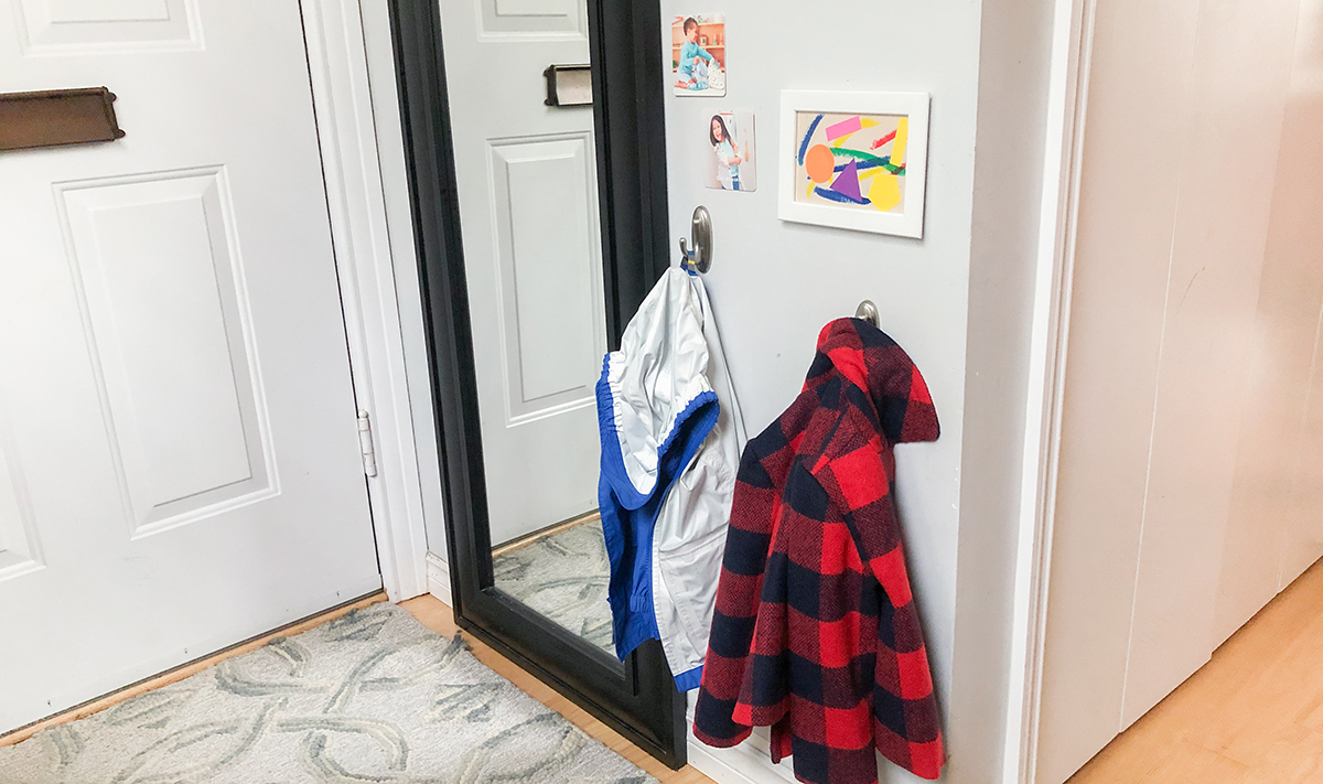 Two hanging jackets and a mirror next to the front door