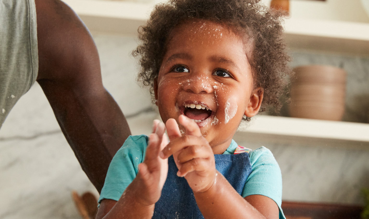 Toddler smiling with flour on their face