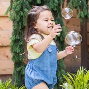34-36 month old child outside playing with bubbles