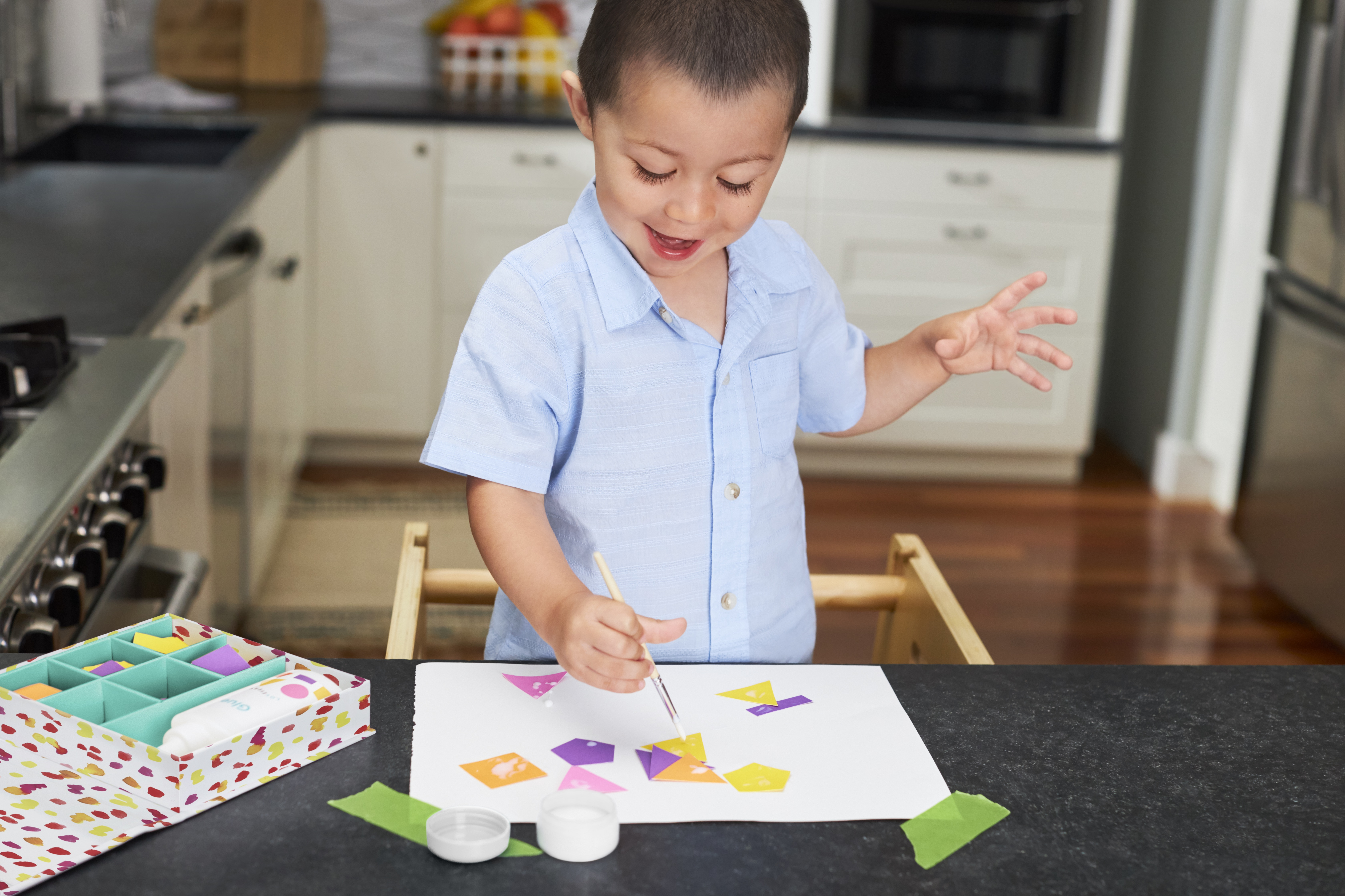 Young child playing with the Sticky Shapes Glue Station by Lovevery