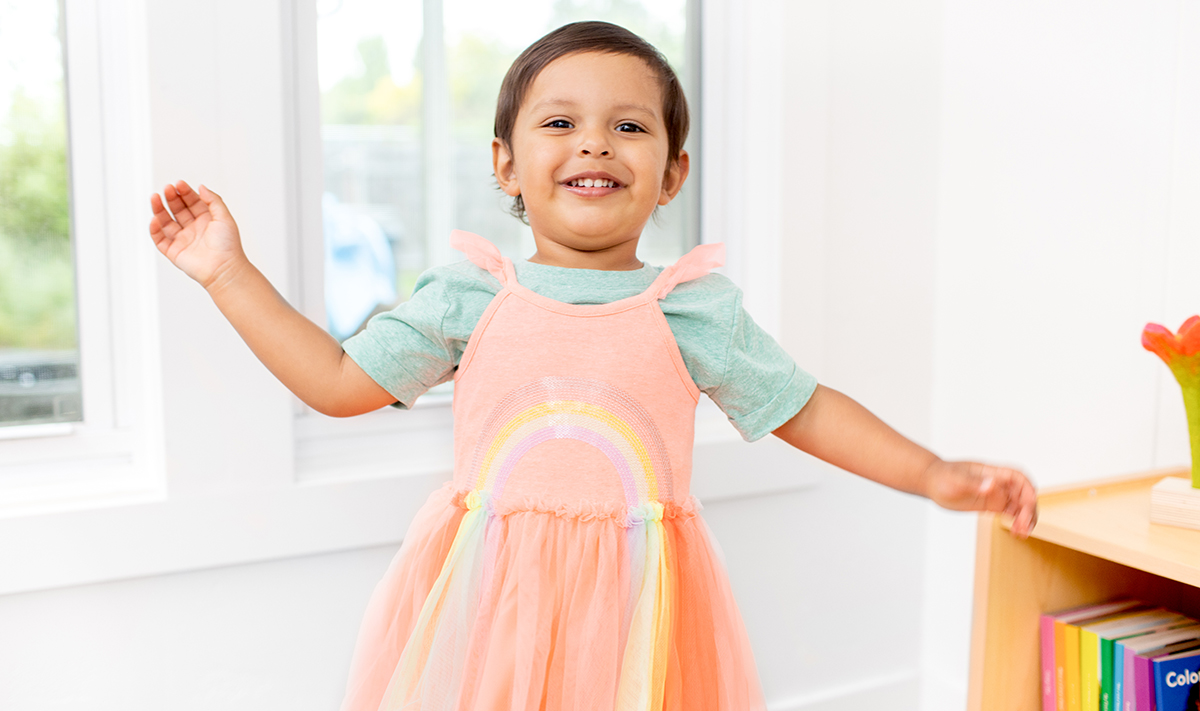 Child wearing a rainbow dress.