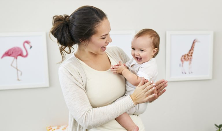 Woman holding a clapping baby on her hip