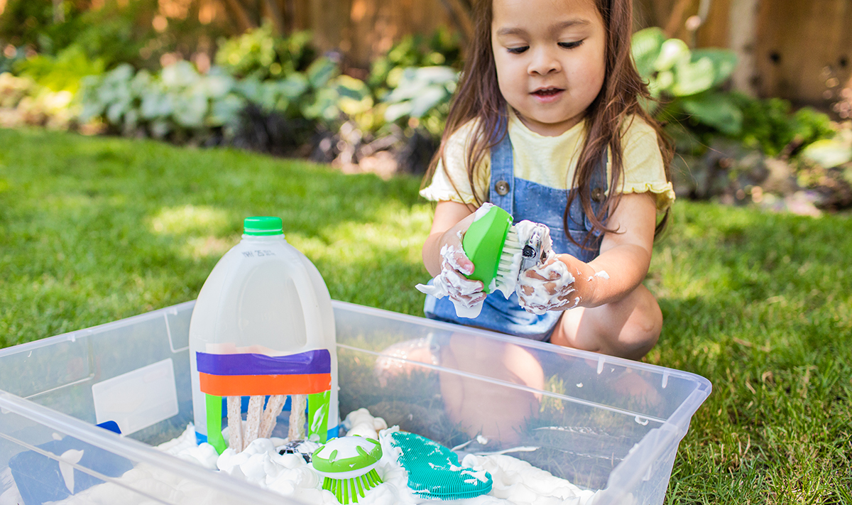 Child plays with suds in a water table.