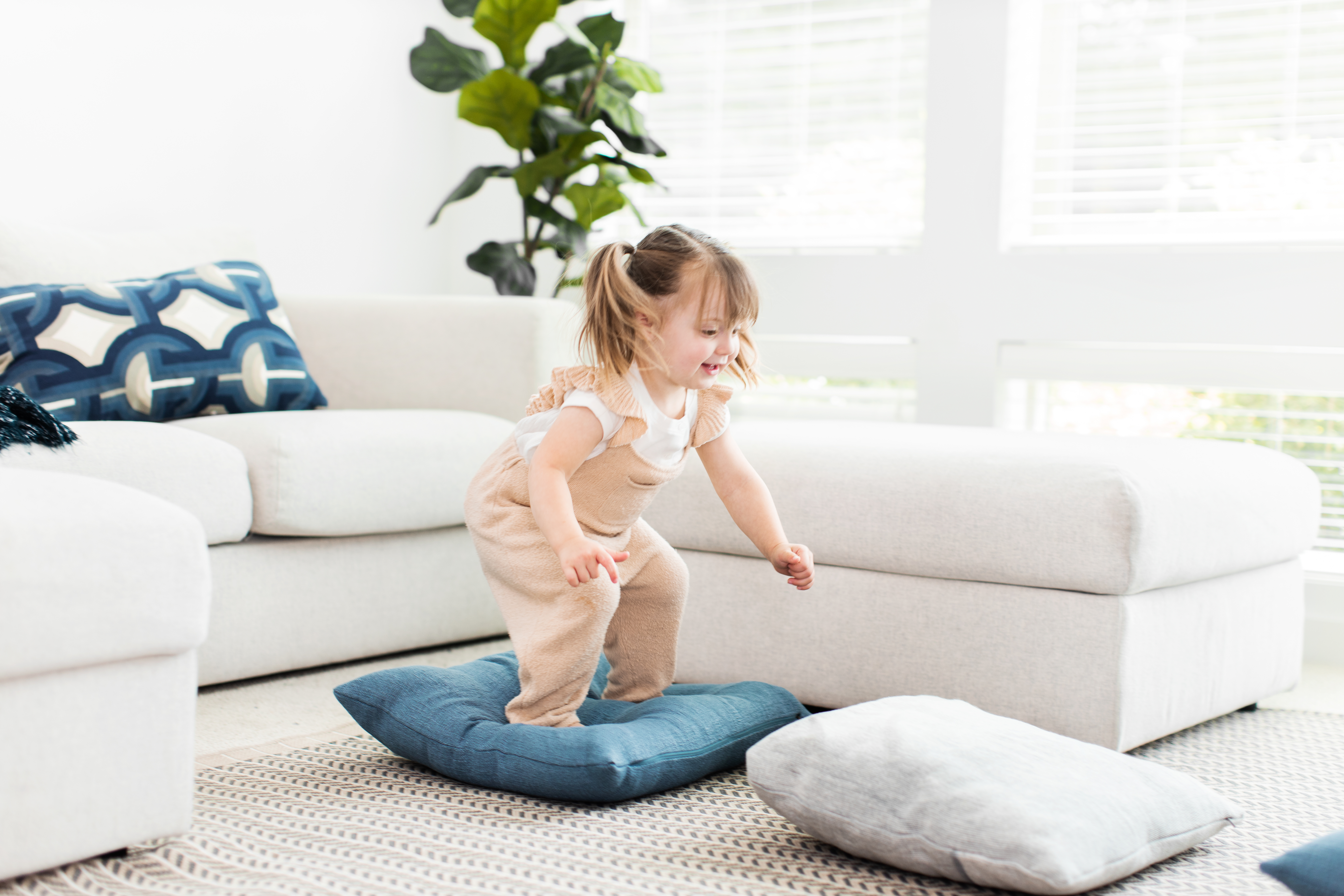 Toddler jumping from a pillow to another pillow on the ground