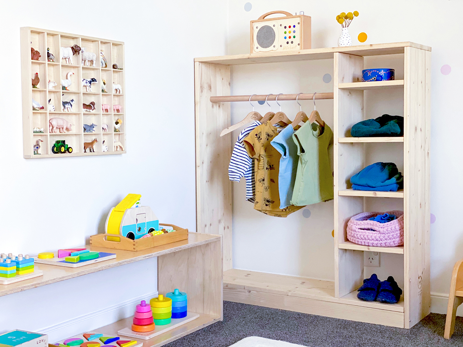 Montessori bedroom with built in closet and table with colorful toys by Lovevery on top