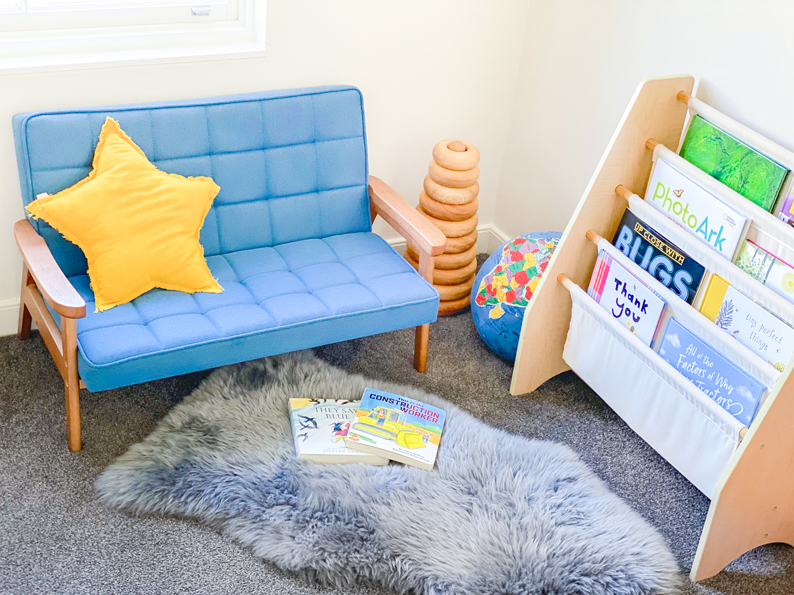 Montessori bedroom corner with small couch and book holder