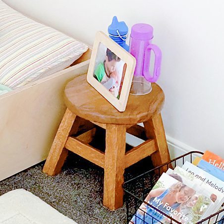 Wooden stool with picture frame and flashlight on it