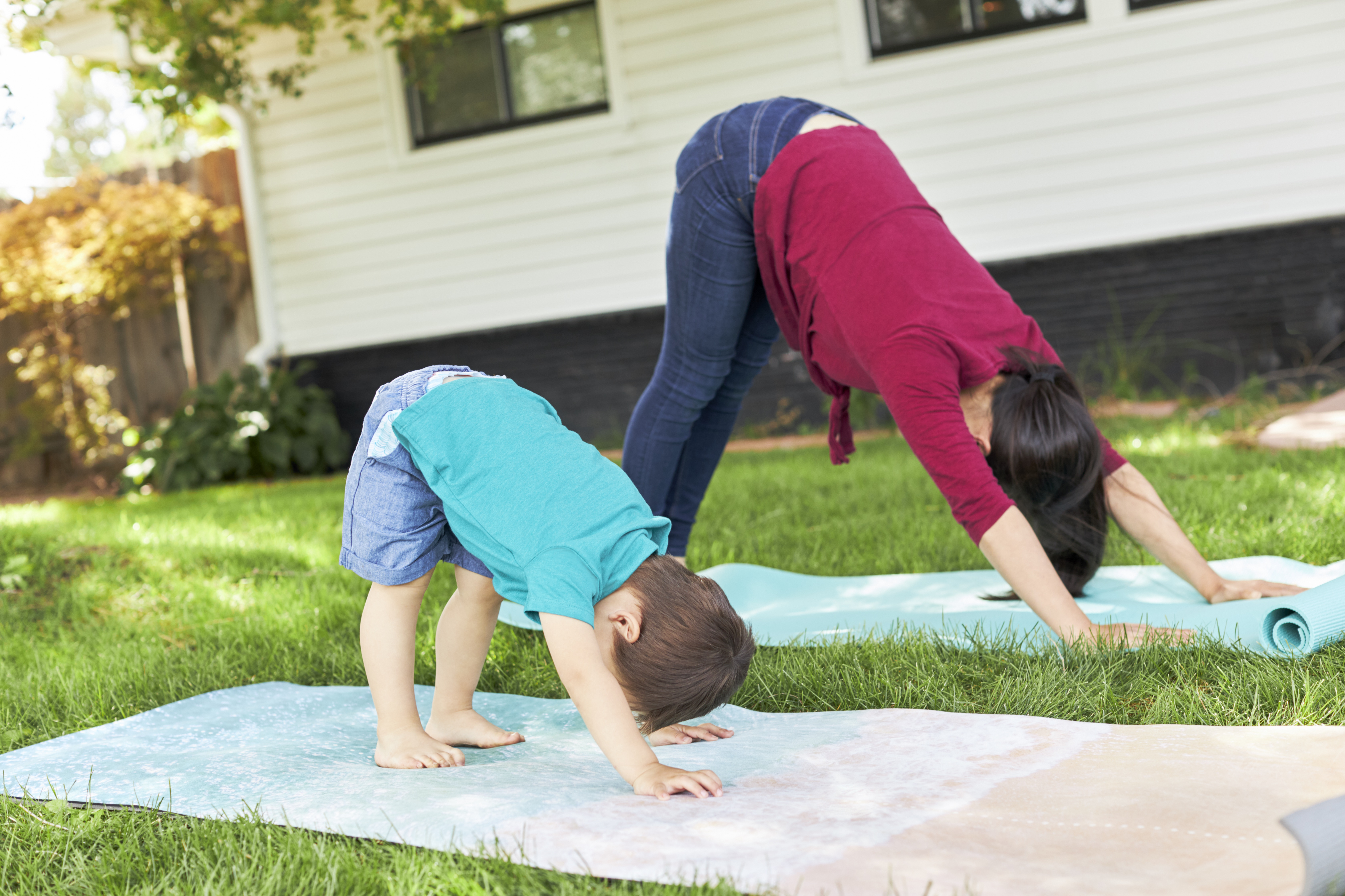 Toddler and woman doing the yoga position down dog outside on the grass