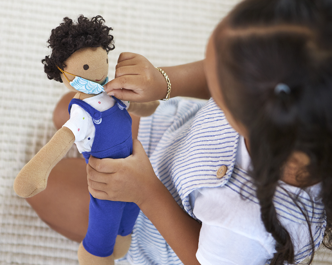 Toddler looking at a Cotton Doll and touching their mask