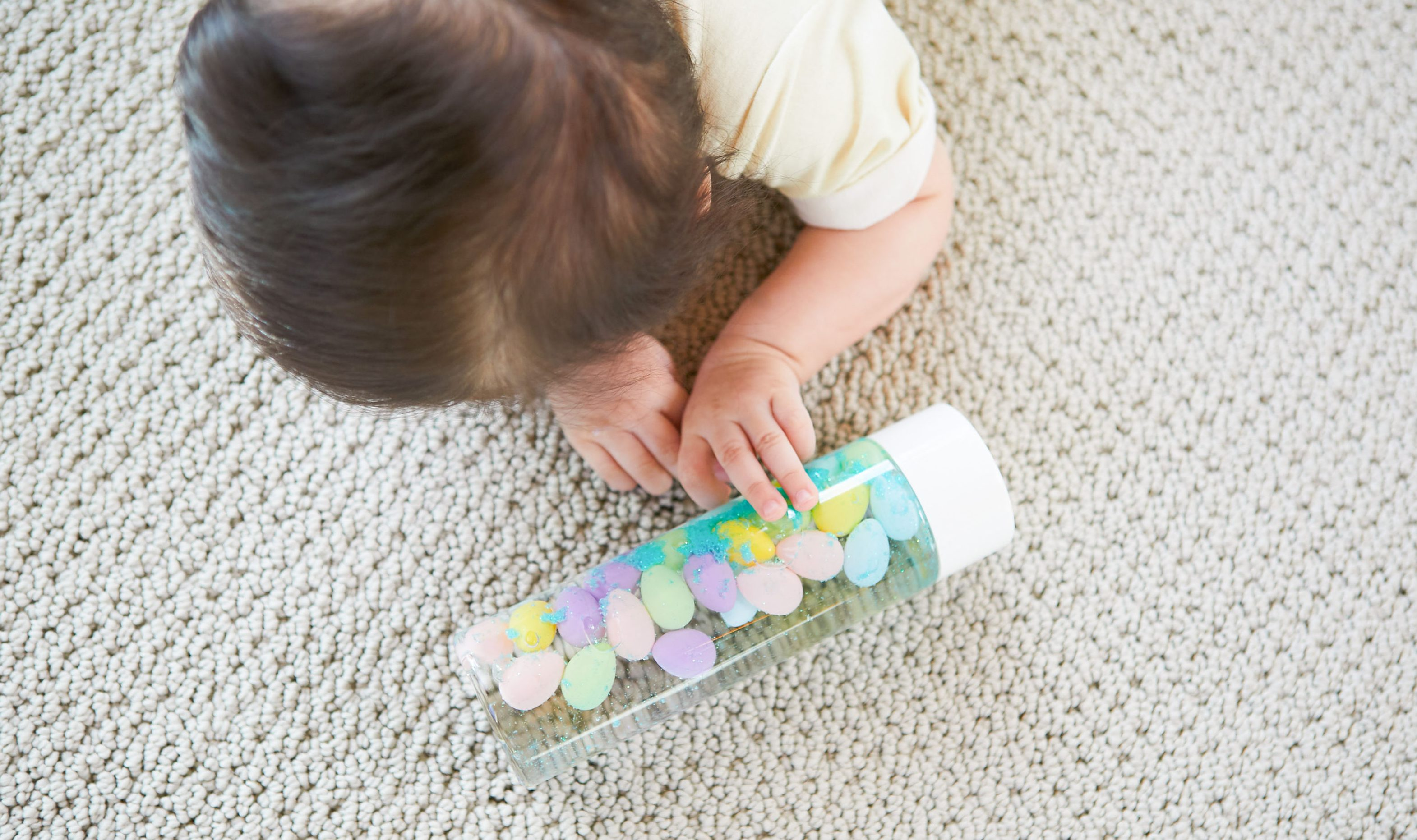 Baby doing tummy time and looking at a water bottle filled with different colors