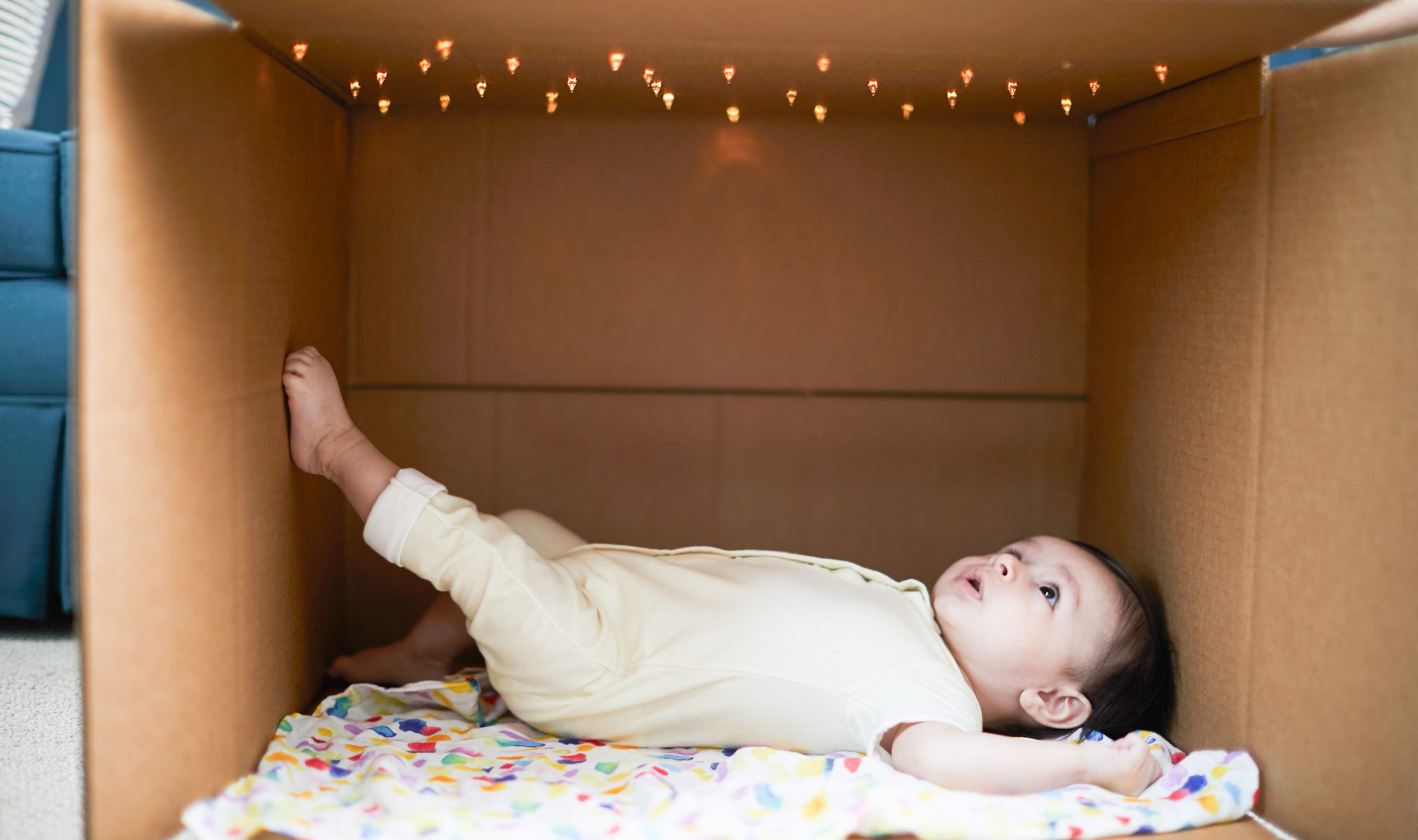 Baby laying in a cardboard box looking up at lights