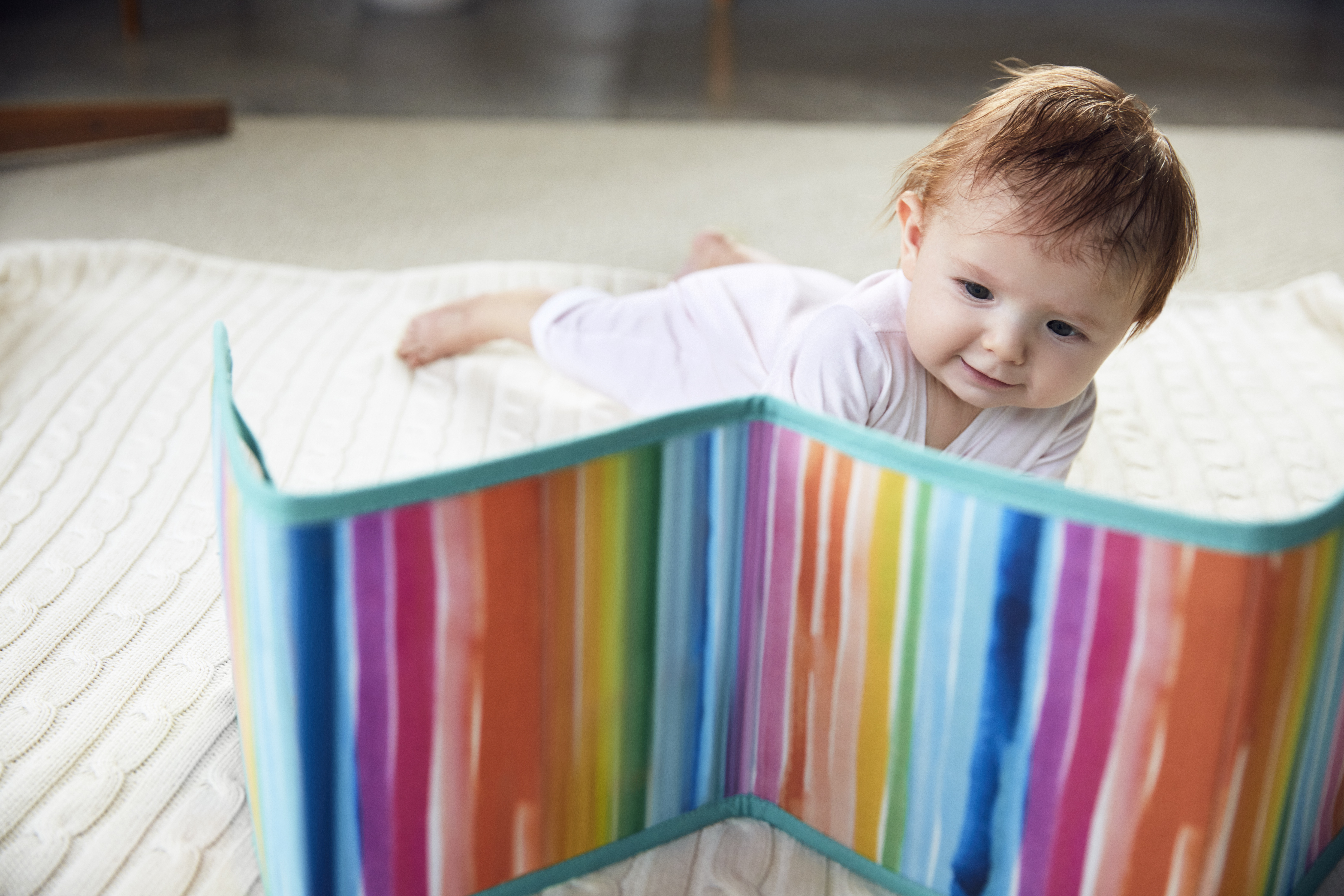 Baby doing tummy time while looking at the Standing Card Holder by Lovevery