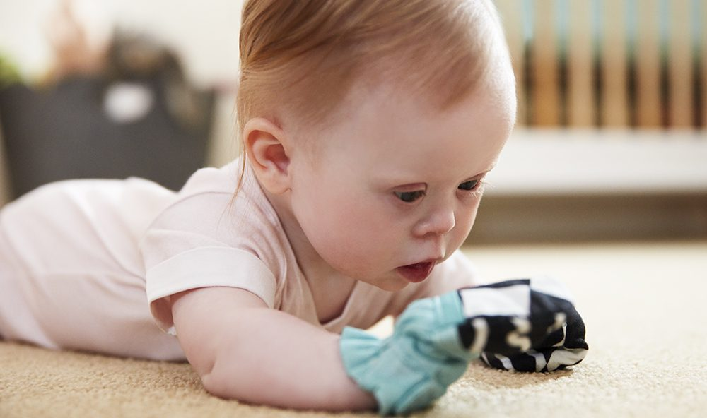 Baby doing tummy time and looking at their hands while wearing the Black and White Mittens