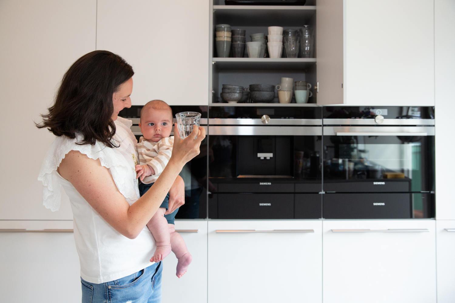 Woman holding baby in a kitchen while holding a glass