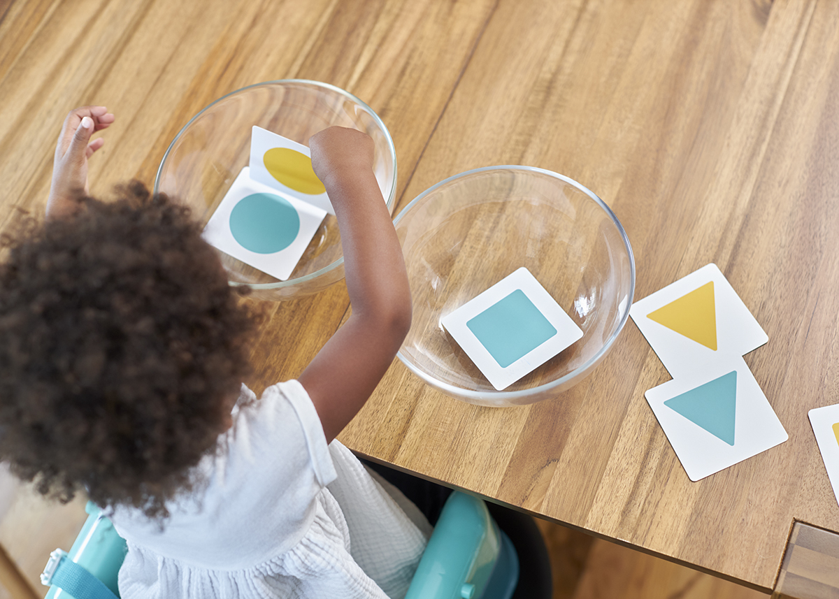 Toddler sorting different colors and patterns into two mixing bowls