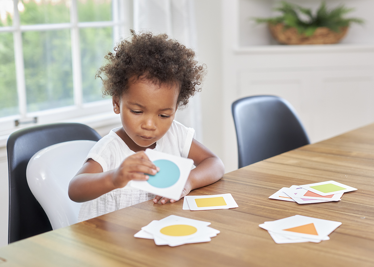 Toddler sorting different colors and patterns on the kitchen table