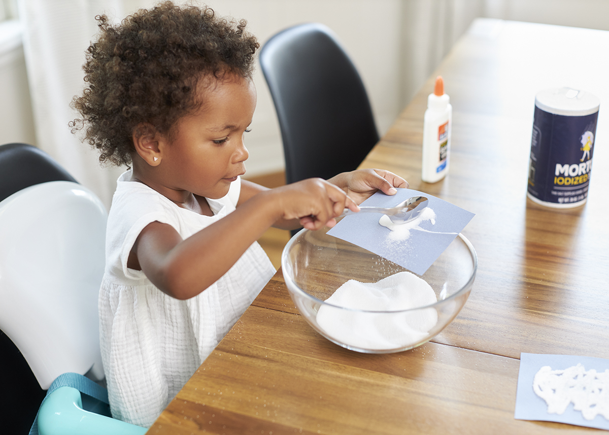 Young child holding a piece of paper with glue on it and pouring salt on top.