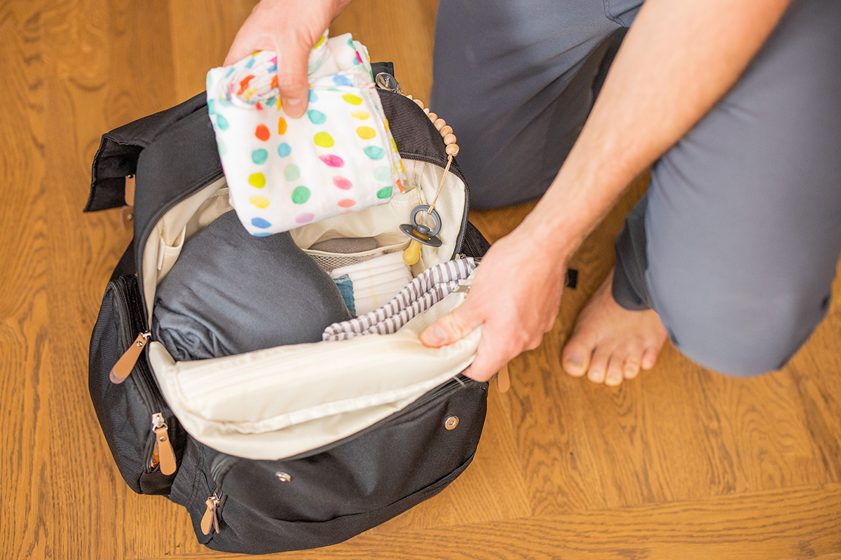 Adult putting colorful items into their diaper bag