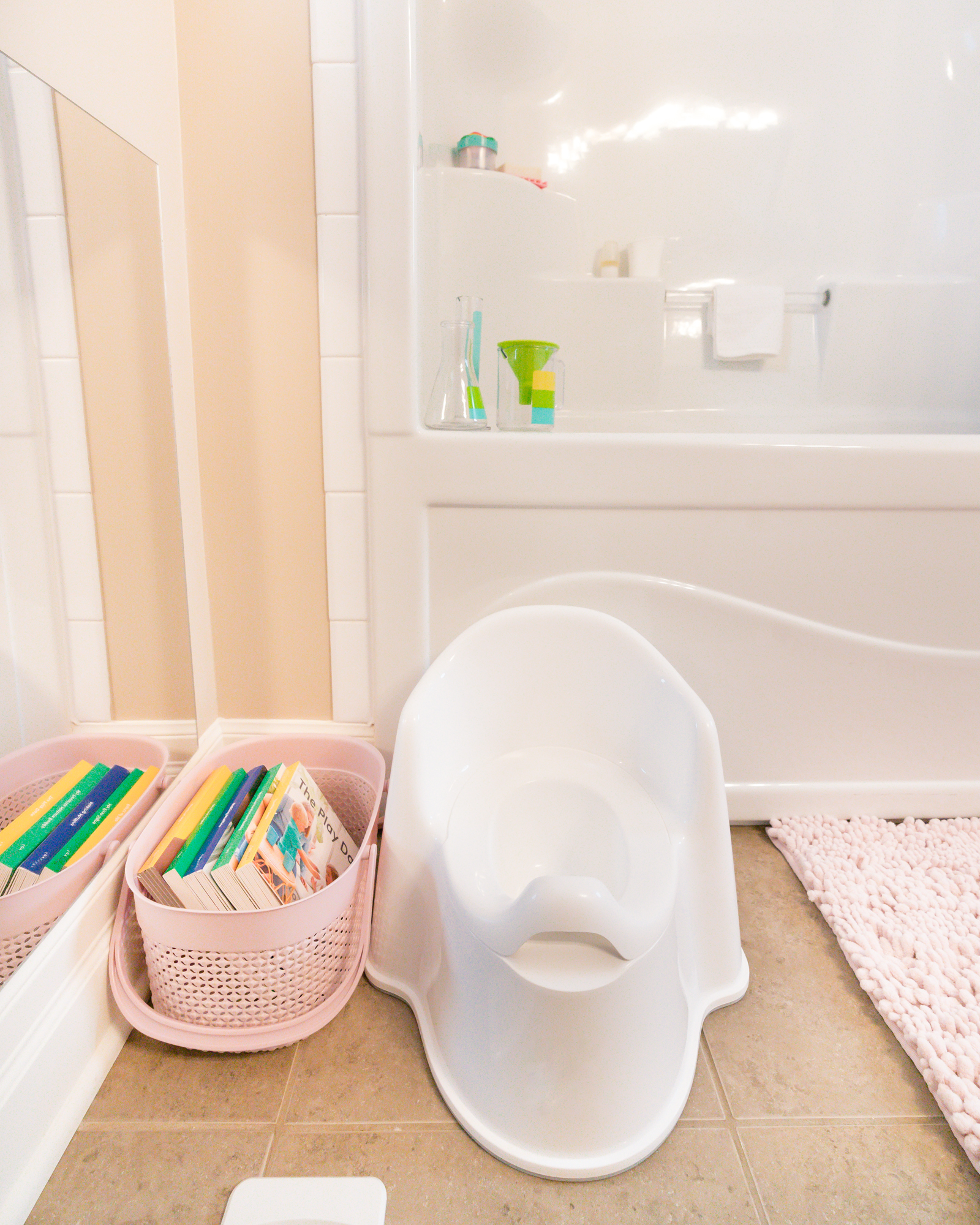 Potty seat and a basket of books next to a bathtub in a bathroom