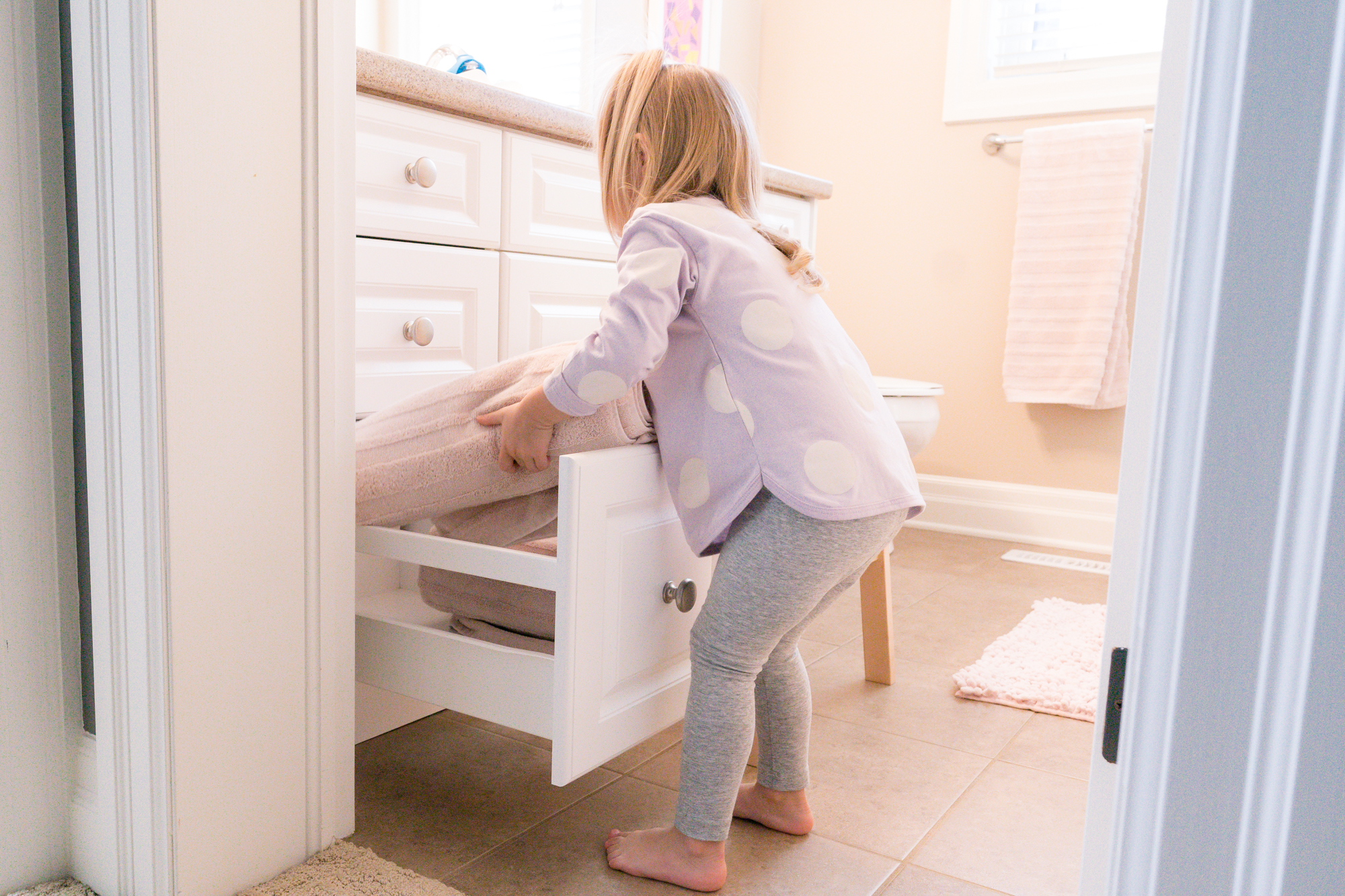 Young child putting towels away in a drawer in a bathroom
