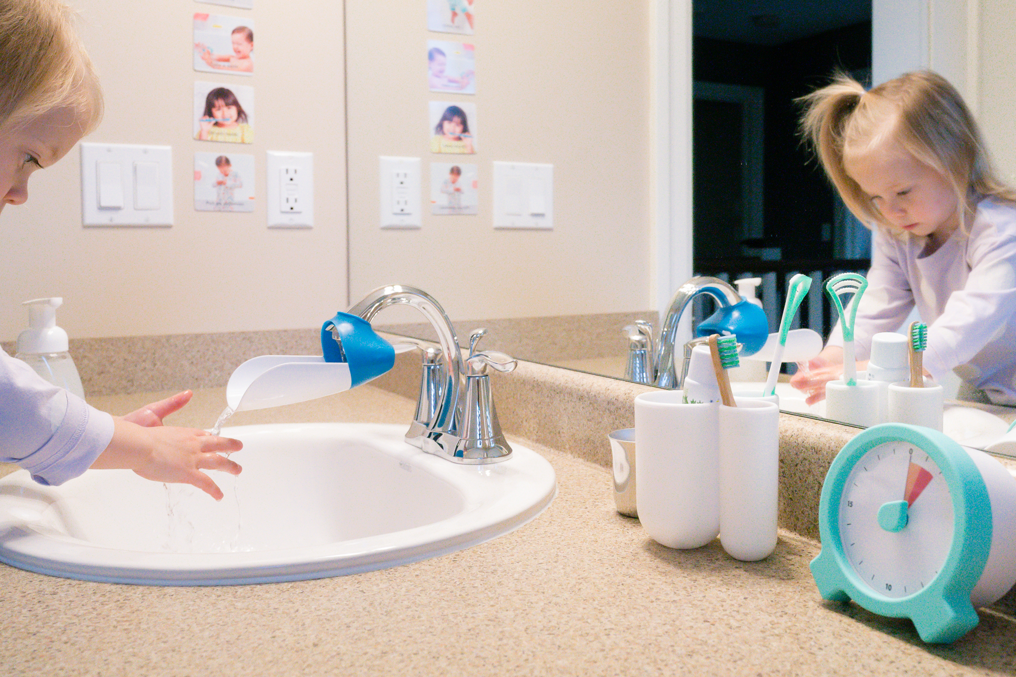 Young child washing their hands in a bathroom sink