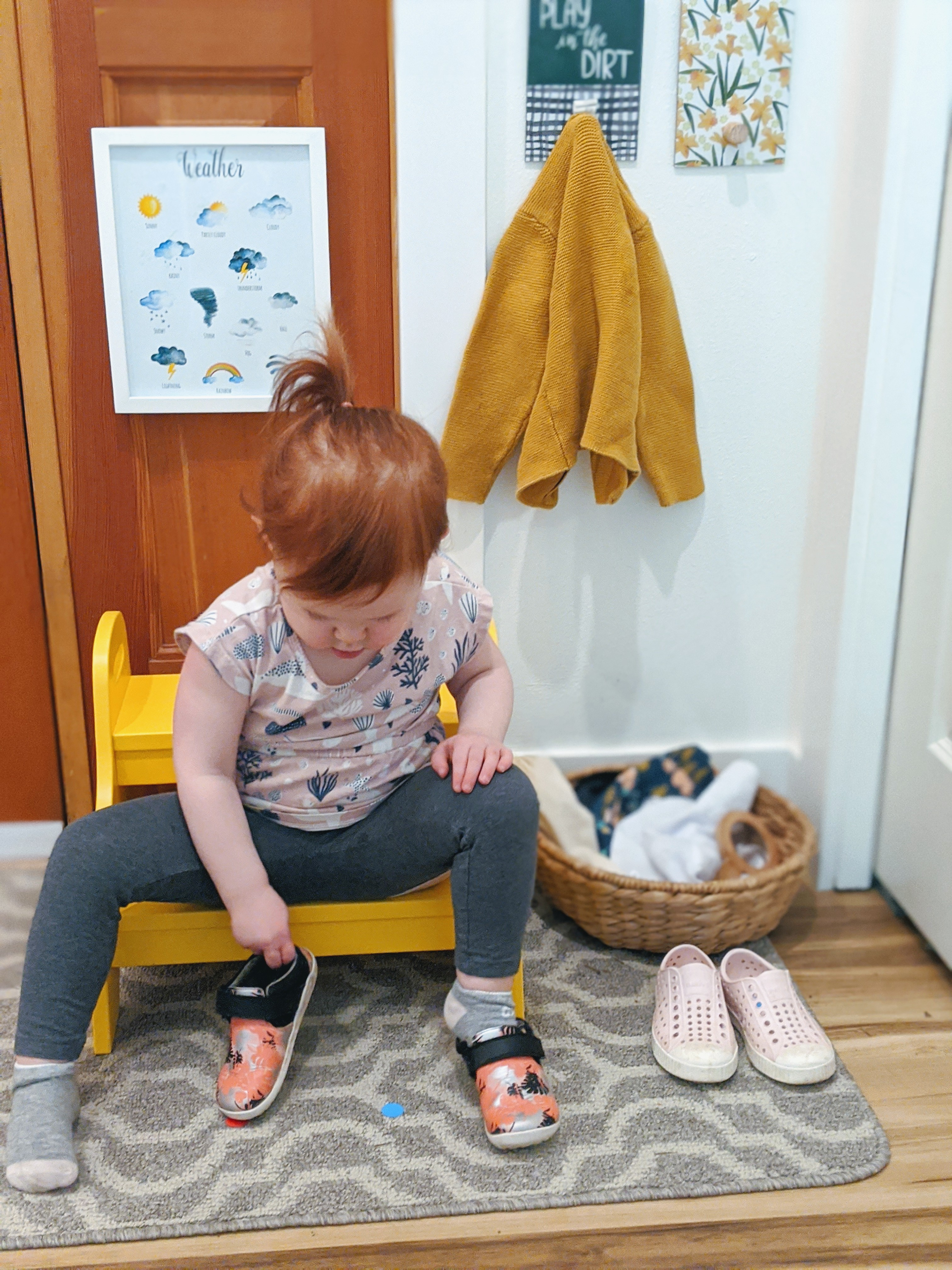 Toddler sitting on a stool putting on their shoes