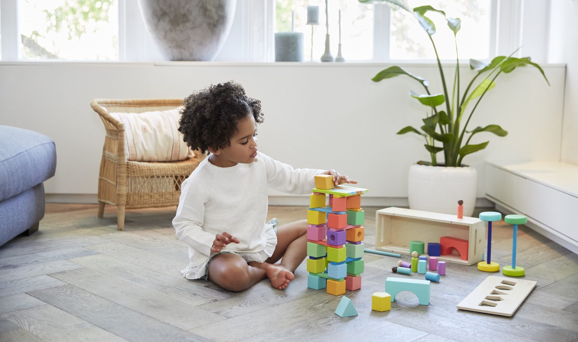 Young child sitting on the floor building a tower with The Block Set by Lovevery