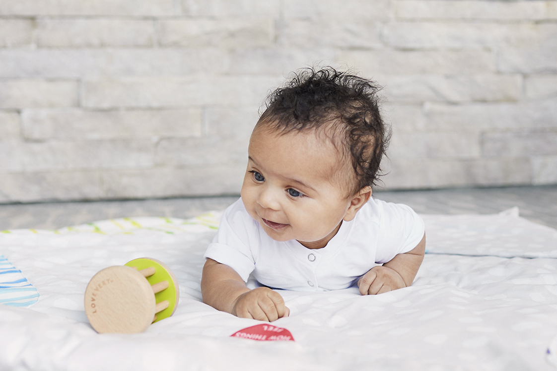 Baby doing tummy time and playing with the Rolling Bell by Lovevery