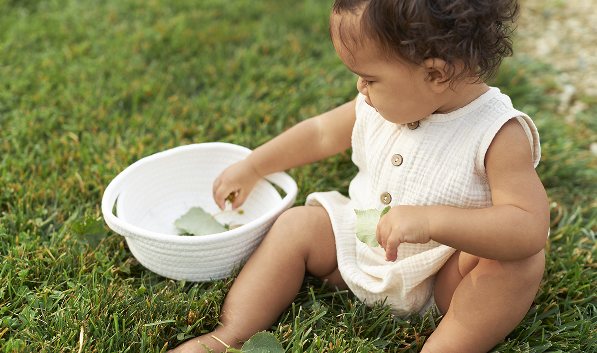 Baby sitting on the grass putting leaves in a basket