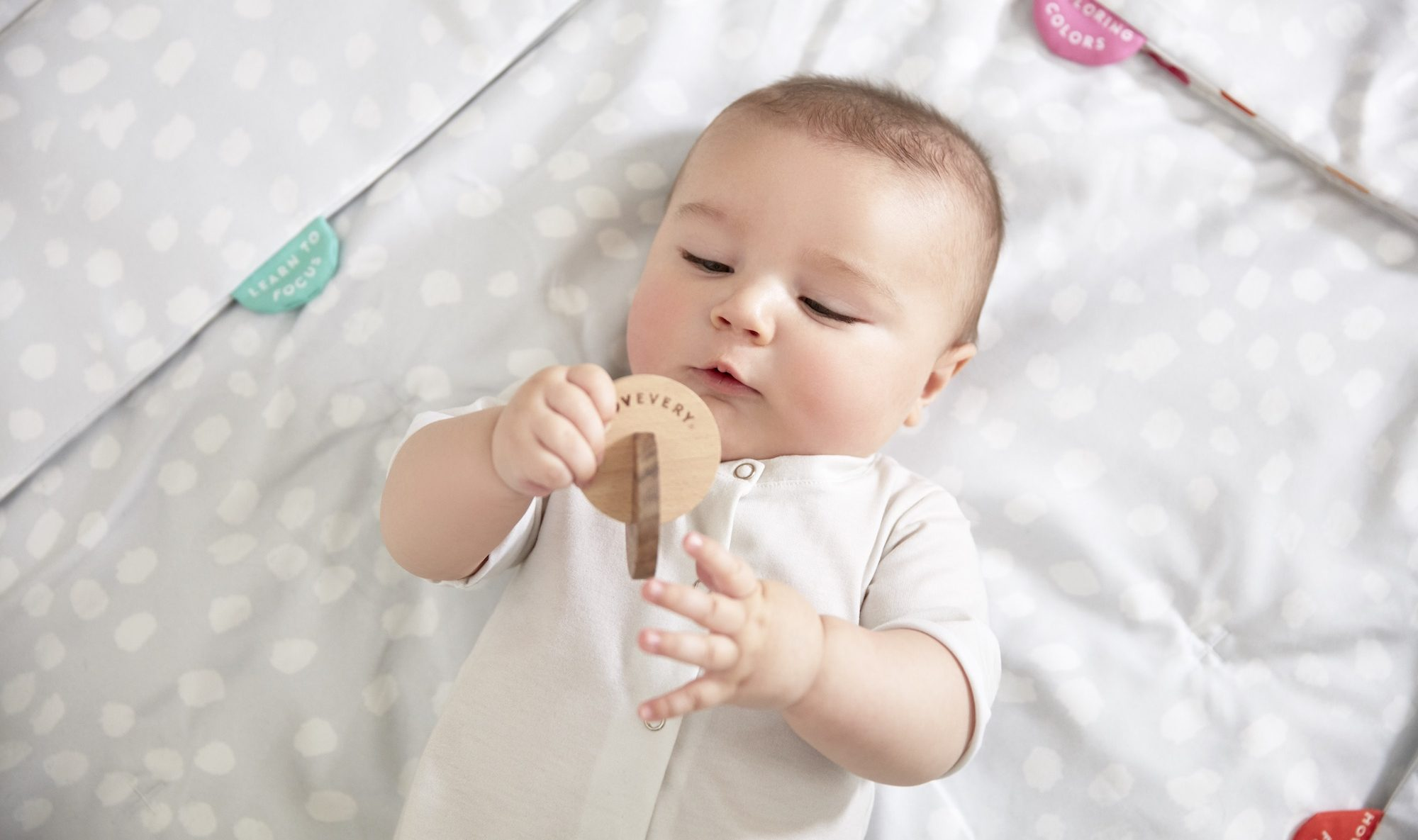 Baby laying down and holding a wooden toy by Lovevery