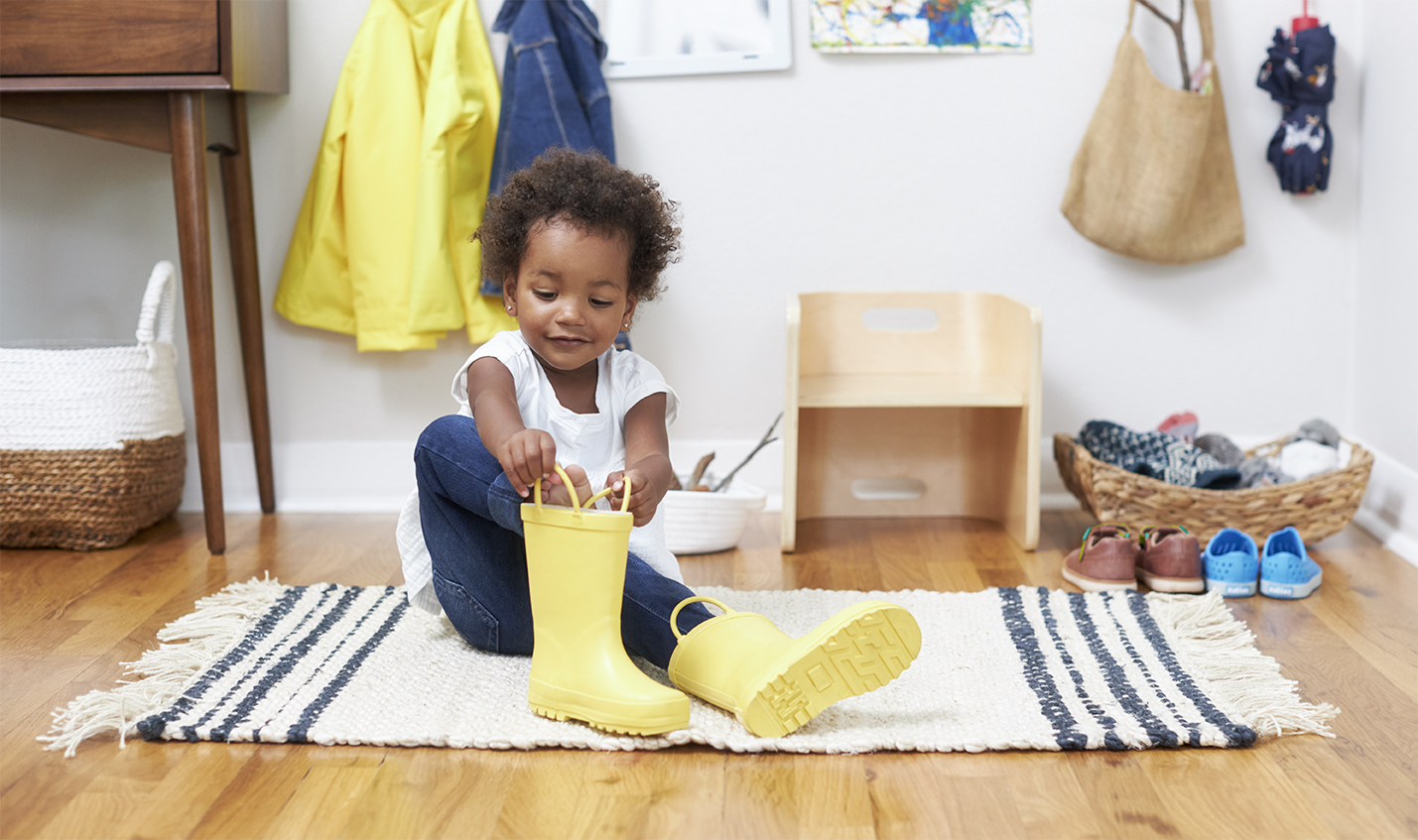 Little girl puts on her own boots.