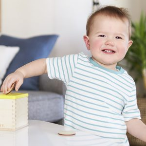Toddler putting wooden coins in a wooden box by Lovevery