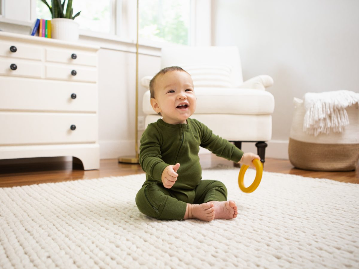 Baby sitting up on a rug with a toy