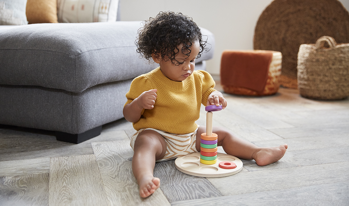 Toddler playing with a Lovevery stacking toy