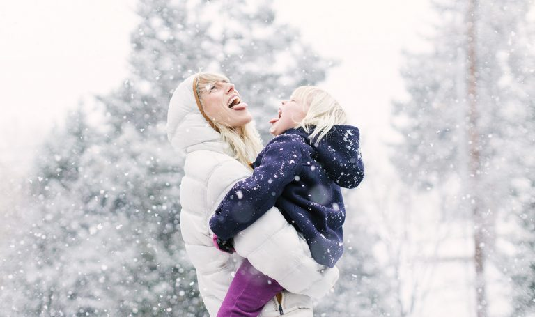 Mother collects snowflakes on her tongue with her daughter.