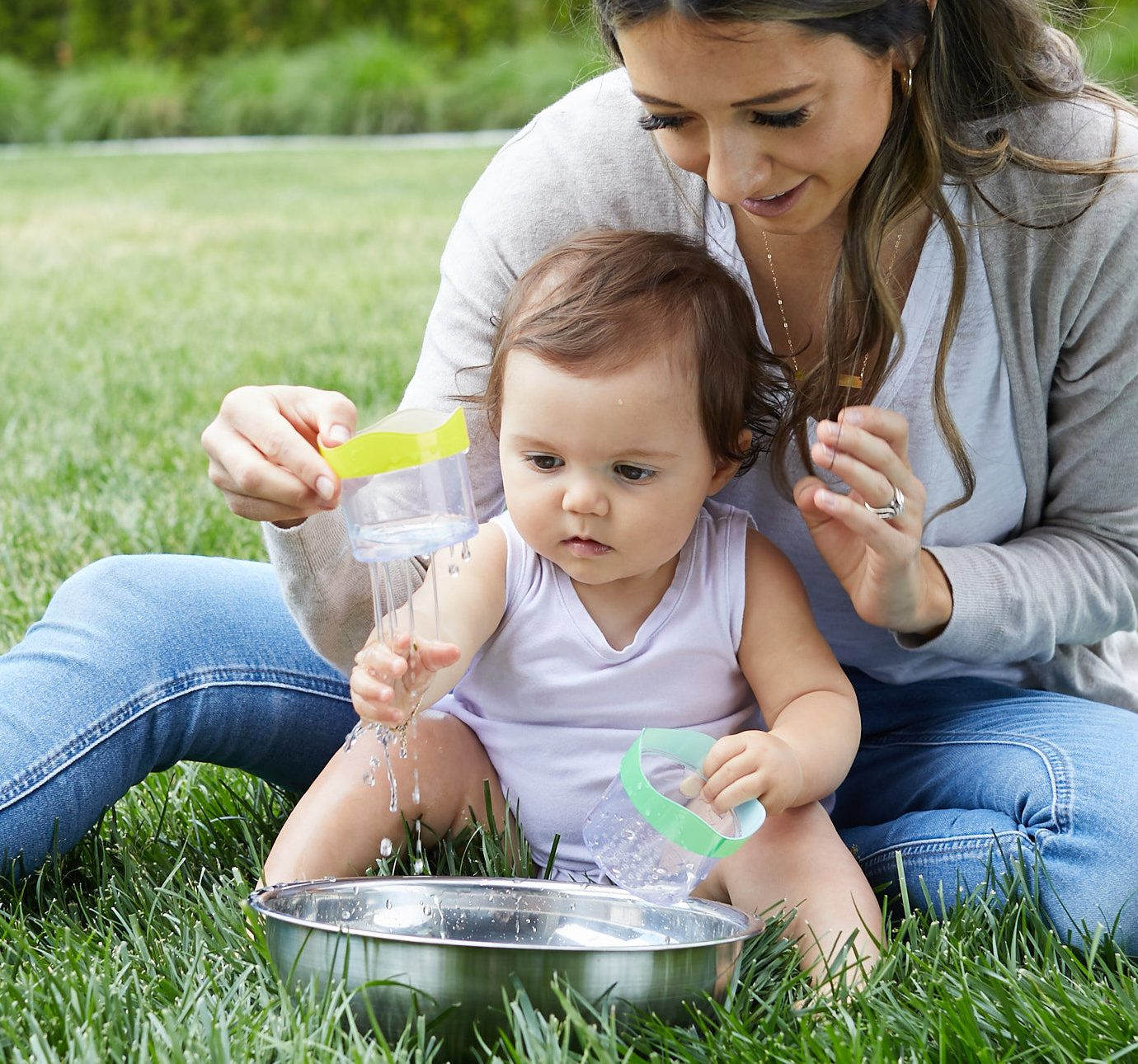 Woman and baby playing outside with the Lovevery Drip Drop cups