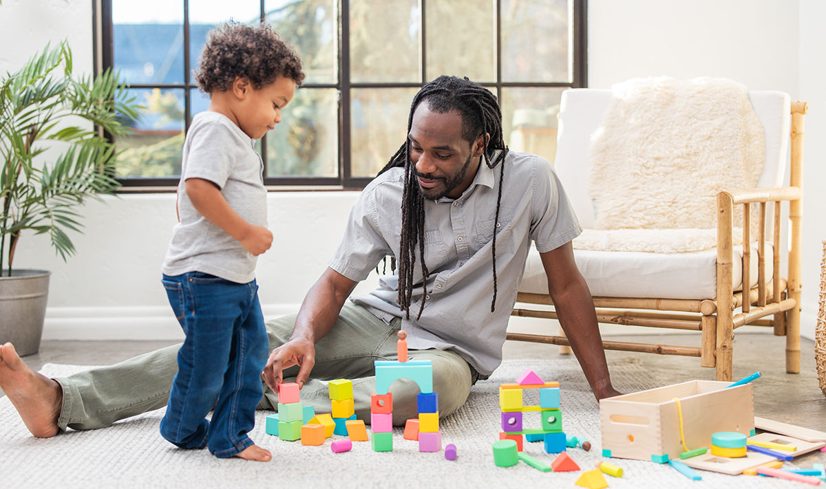 Man and toddler playing with The Block Set by Lovevery