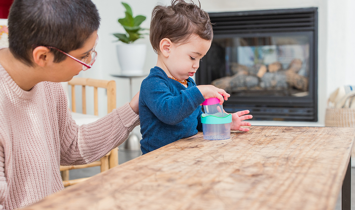 Toddler sitting at a table stacking the Nesting Stacking Drip Drop Cups by Lovevery
