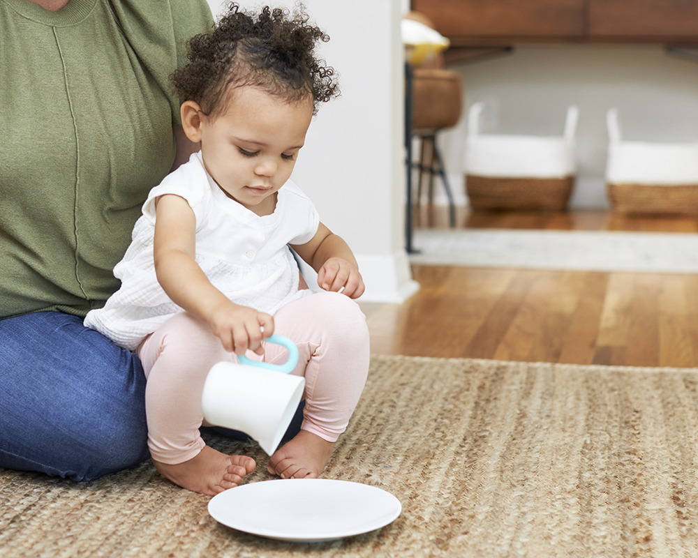 Toddler pretending to pour a liquid from a cup to a plate