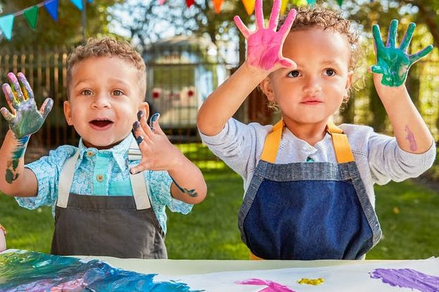 Two young children holding up their hands that have paint on them