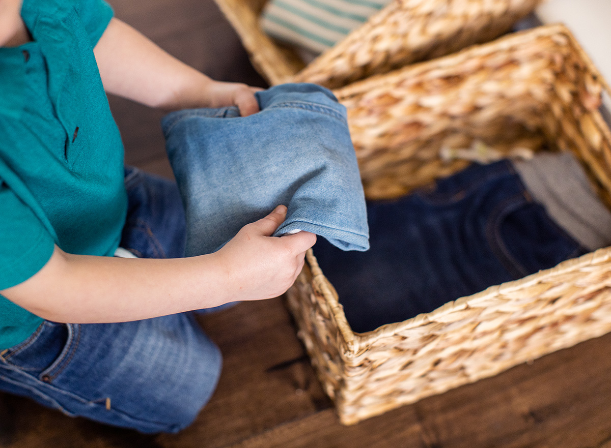 Young child putting a pair of folded jeans into a basket