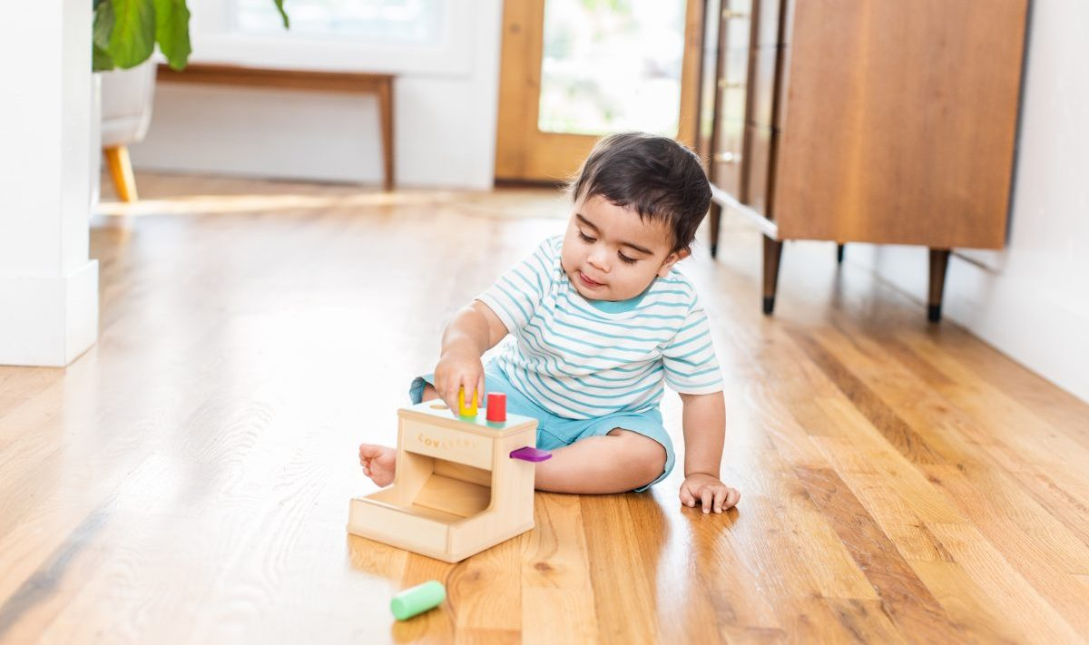 Toddler playing with the Wooden Peg Drop